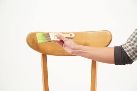 Hand holding paint brush over chair. PaintCare Inc  Can You Repurpose Latex Wall Paint for Use On Wood